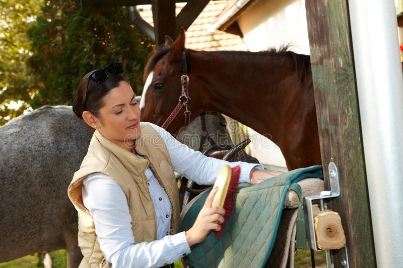 Young woman grooming horse. Young woman cleaning horse saddlery outdoors, brushing saddle-cloth royalty free stock photos