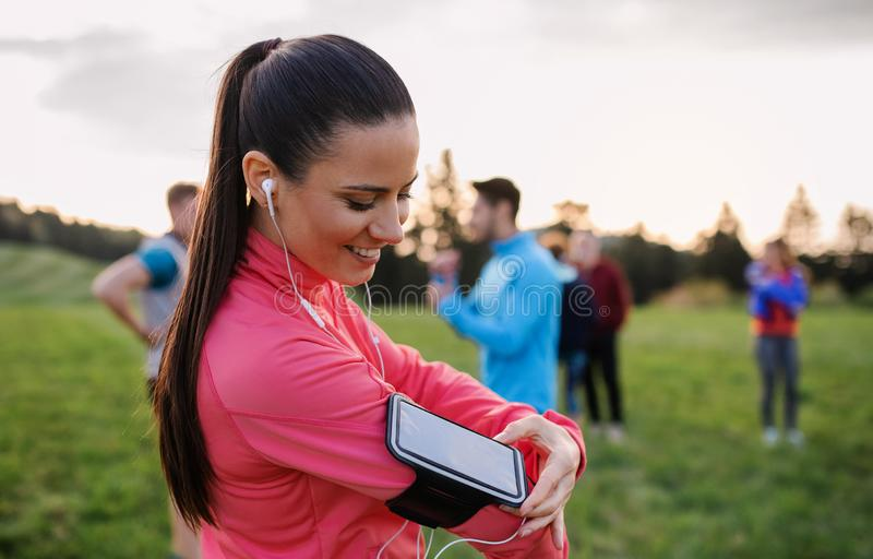 A young woman with group of people doing exercise in nature, resting. A portrait of young women with earphones and group of people doing exercise in nature stock photos
