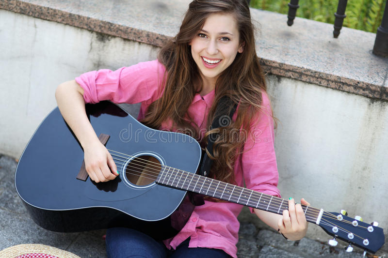 Download Young woman with a guitar stock image. Image of city - 24916427
