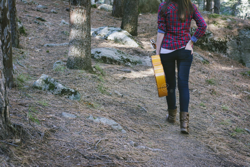 Young woman with a guitar in hand, walking back through the fore stock photos