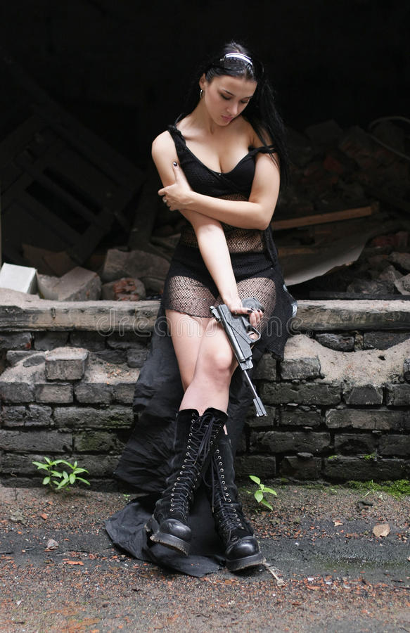 Young woman with gun in the big boots stock photography