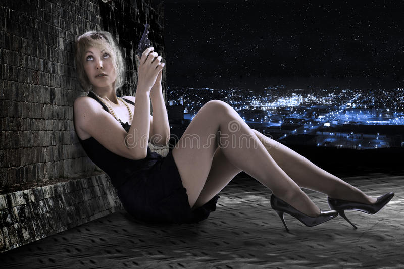 The young woman with the gun on a roof. royalty free stock photo