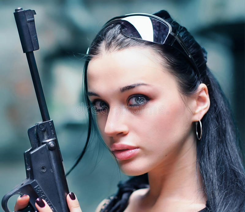 Young woman with gun wearing glasses stock image