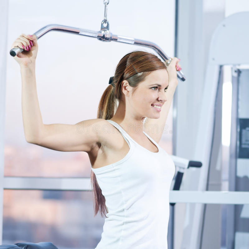 Young woman at the gym. Exercising on a machine stock image