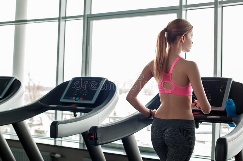 Young girl in gym healthy lifestyle running on treadmill looking out the window thinking back view royalty free stock images