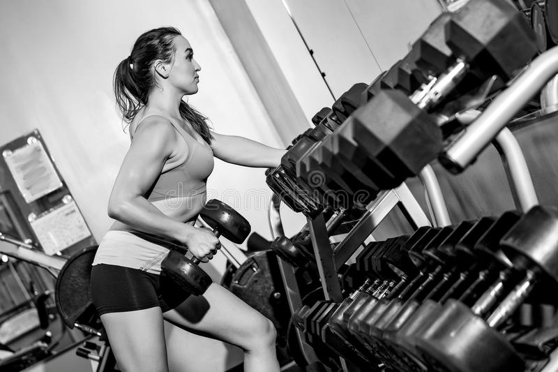 Young woman in the gym lifting weights stock photo