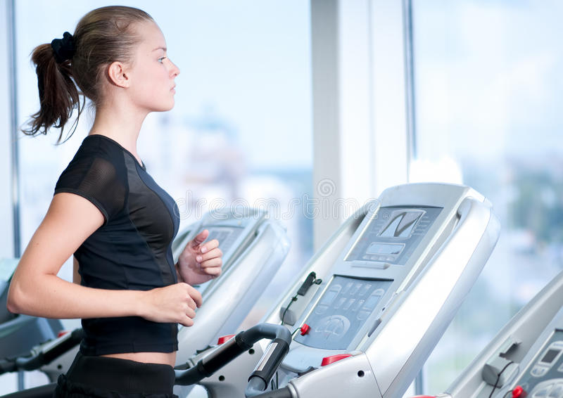 Young woman at the gym. Run on a machine stock photo