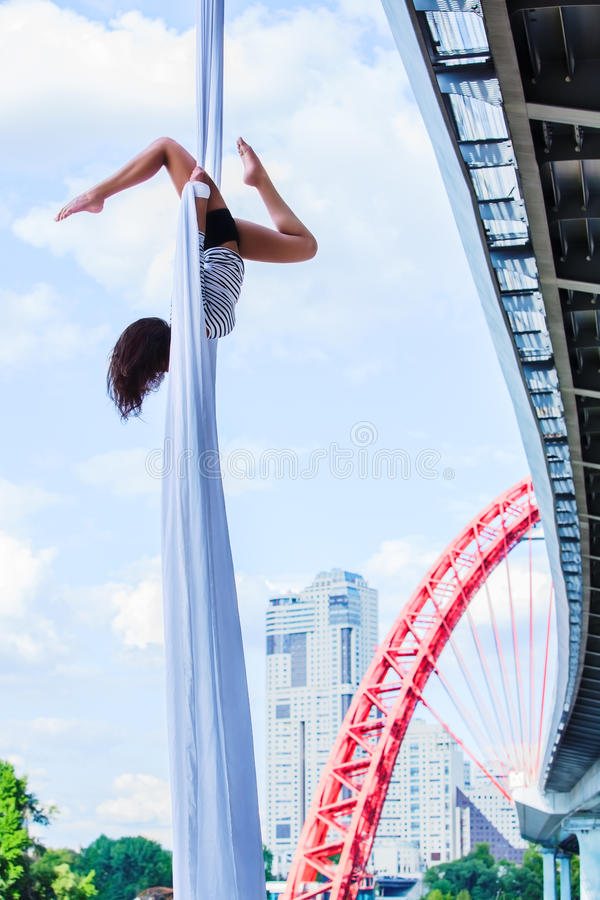 Young woman gymnast. On city and sky background royalty free stock images