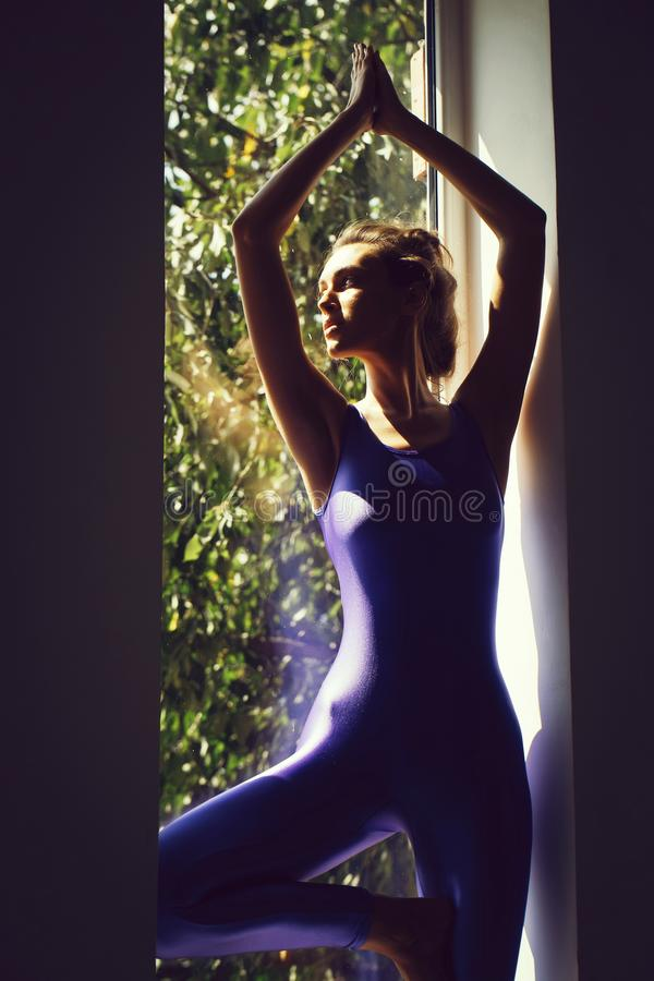 Young sexy woman gymnast. Young woman gymnast with prety face sexy slim body silhouette in blue leotard posing in yoga asana near window indoor stock photo