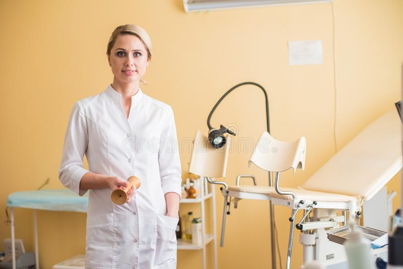 Young woman gynecologist standing behind an armchair. Gynecological chair stock image