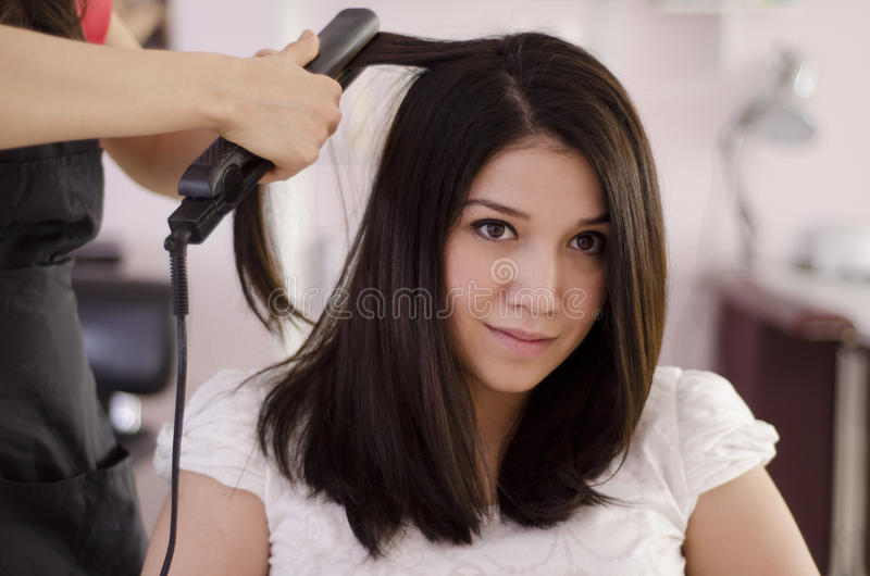Young woman in a hair salon. Beautiful woman getting her hair straightened in a beauty salon stock photo