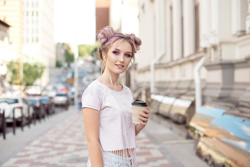 Young woman with a hairstyle a bun and makeup walking in the city listening to music in headphones through the phone in stock photography