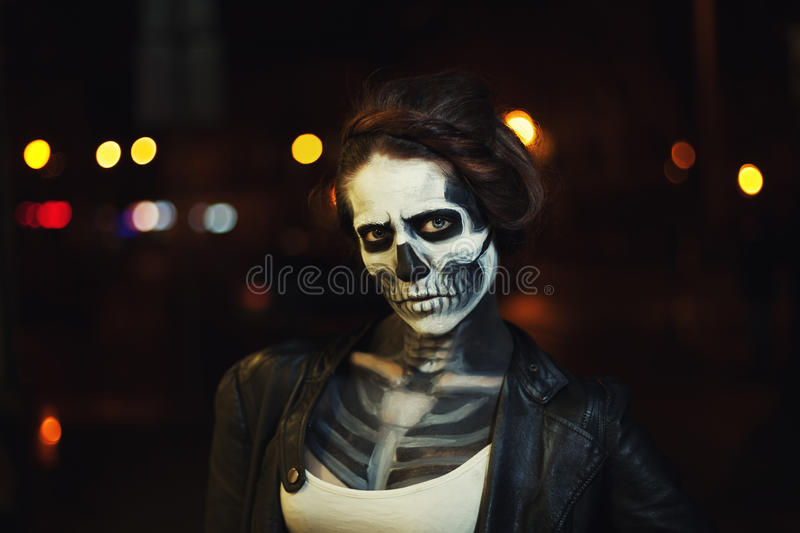 Young woman with Halloween face art. Street portrait. Night city background. Close up stock images