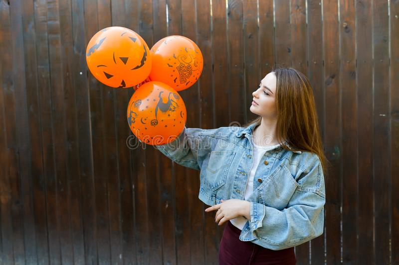Young woman with halloween inflatable orange ballons on brown background, party concept.  stock photo