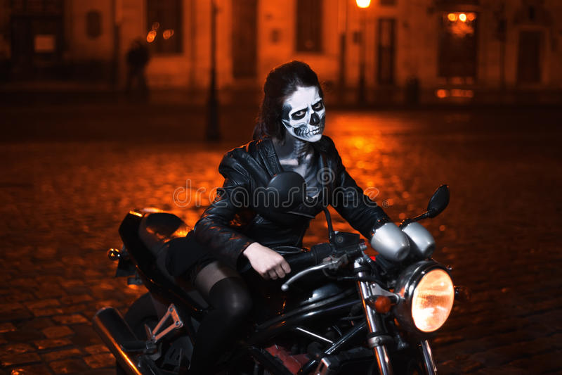 Young woman with Halloween makeup sitting on the motorbike . Street portrait royalty free stock images