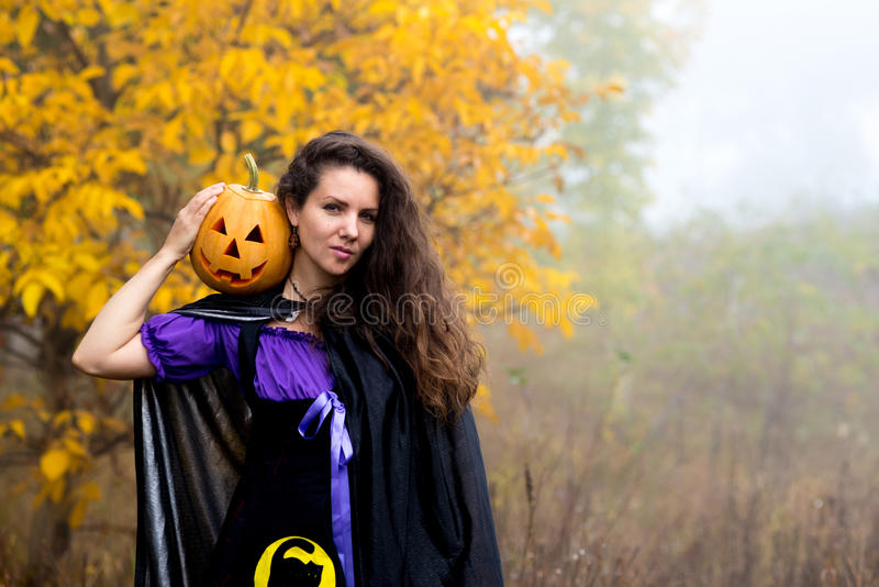 Young woman in Halloween witch costume in the autumn forest with yellow pumpkin. stock images