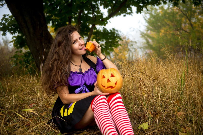 Young woman in Halloween witch costume in the autumn forest with yellow pumpkin. royalty free stock images