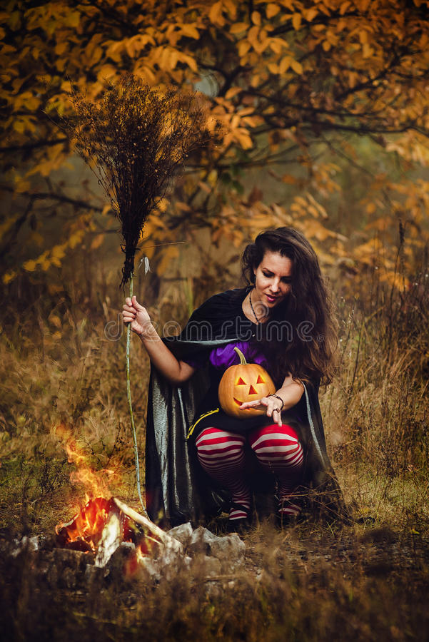 Young woman in Halloween witch costume in the autumn forest with yellow pumpkin. royalty free stock photos