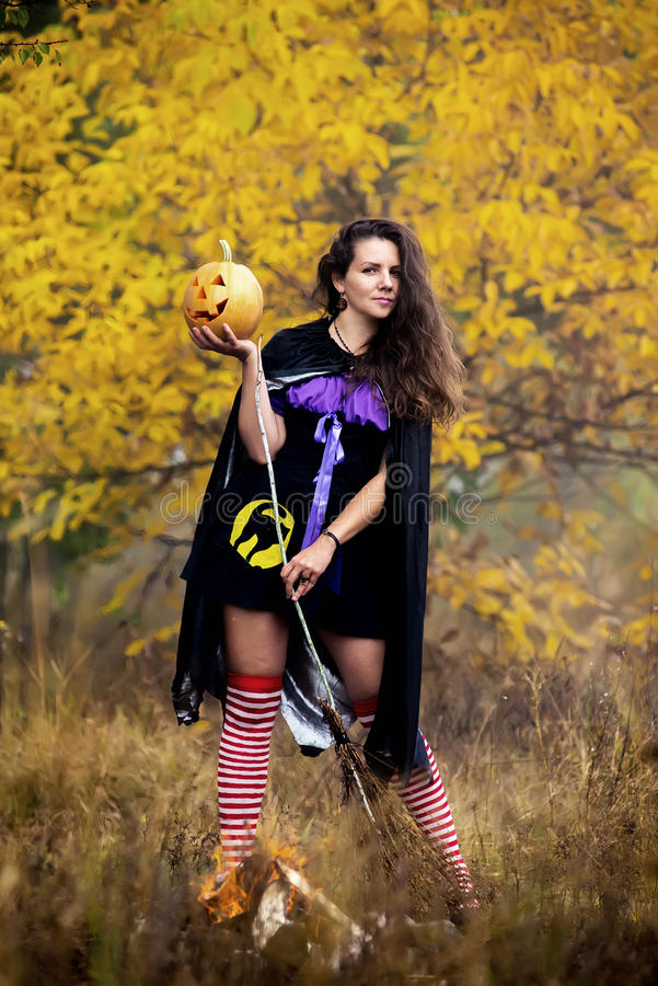 Young woman in Halloween witch costume in the autumn forest with yellow pumpkin. royalty free stock image