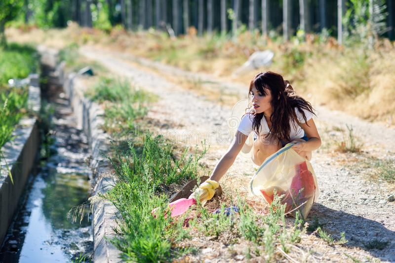 Woman hand collecting garbage of the grass in the countryside royalty free stock image