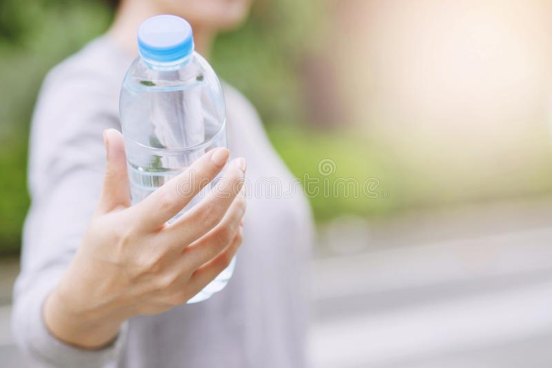 young woman hand holding give fresh drinking water bottle from a plastic in the park royalty free stock photo