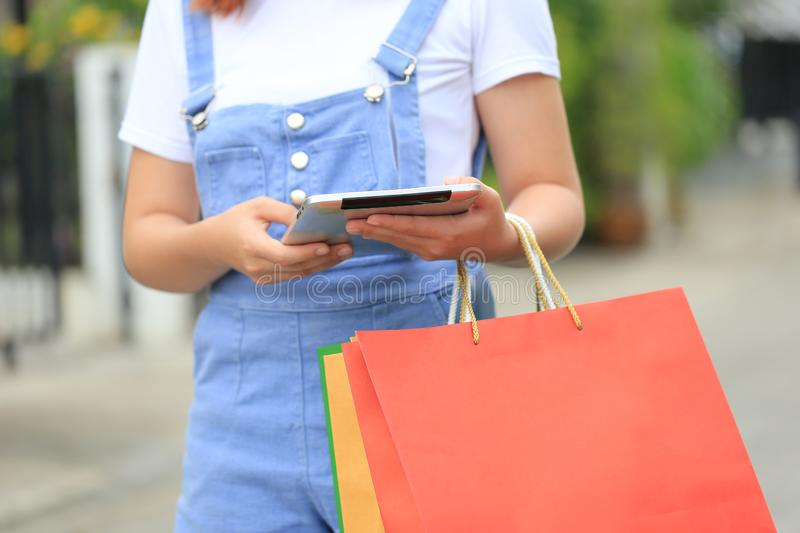 Young woman hand holding tablet smart device and shopping bags with standing at the department store royalty free stock photos