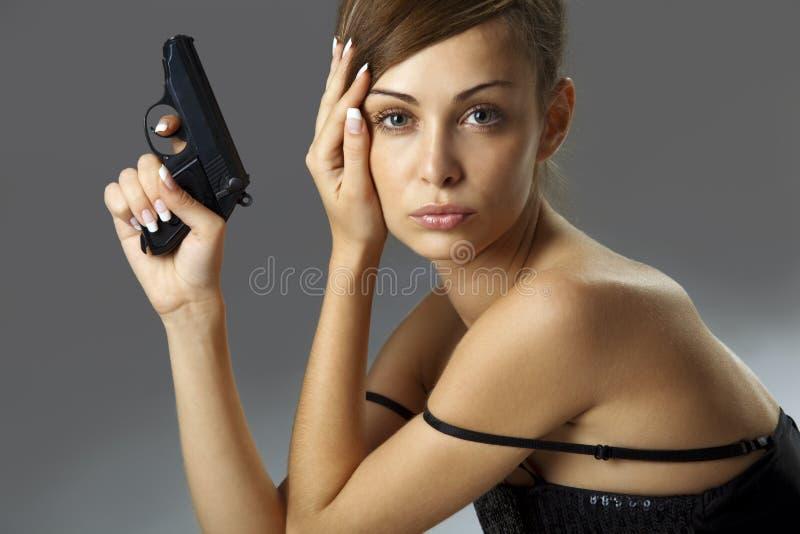 Young woman with handgun royalty free stock photos