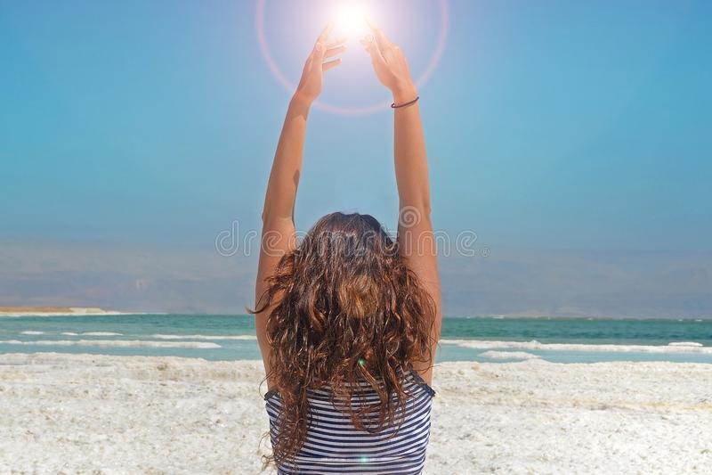 Young woman hands catching the energy of the sun. long-haired girl sits on the shore of the Dead Sea in Israel stock image