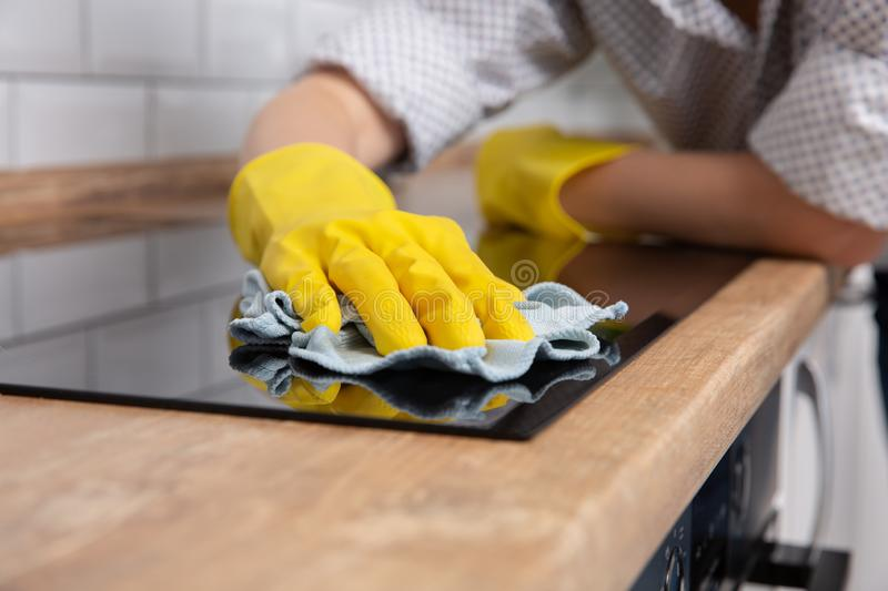 Young woman hands cleaning a modern black induction hob by a rag, housework stock images