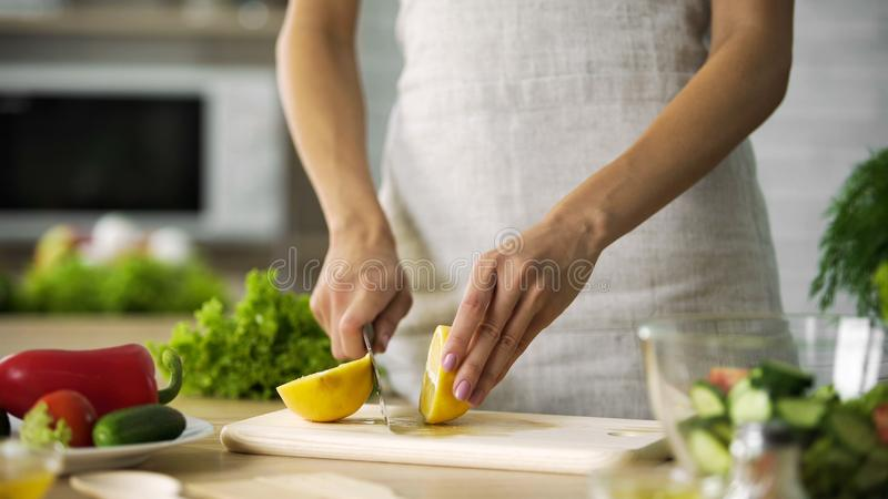 Young woman hands cutting yellow lemon on kitchen board at home, healthy eating royalty free stock photos