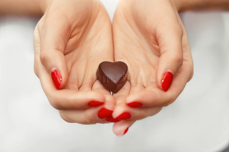 Young woman hands with dark chocolate in a shape of a heart. Enjoy healthy lifestyle. Chocolate candy. Happy days at home. royalty free stock image