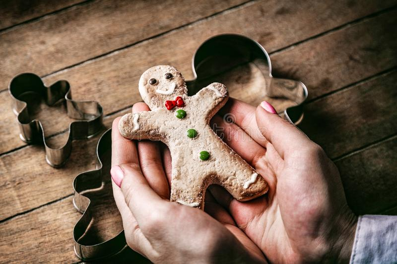 Christmas gingerbread man cookie with forms. Young woman hands holding christmas gingerbread man cookie with forms on wooden background, Photo in old color image stock photo