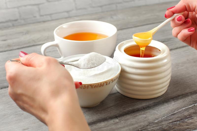 Young woman hands holding spoon of sugar, and honey deciding what to put in tea. Refined vs natural sweetener concept. royalty free stock image