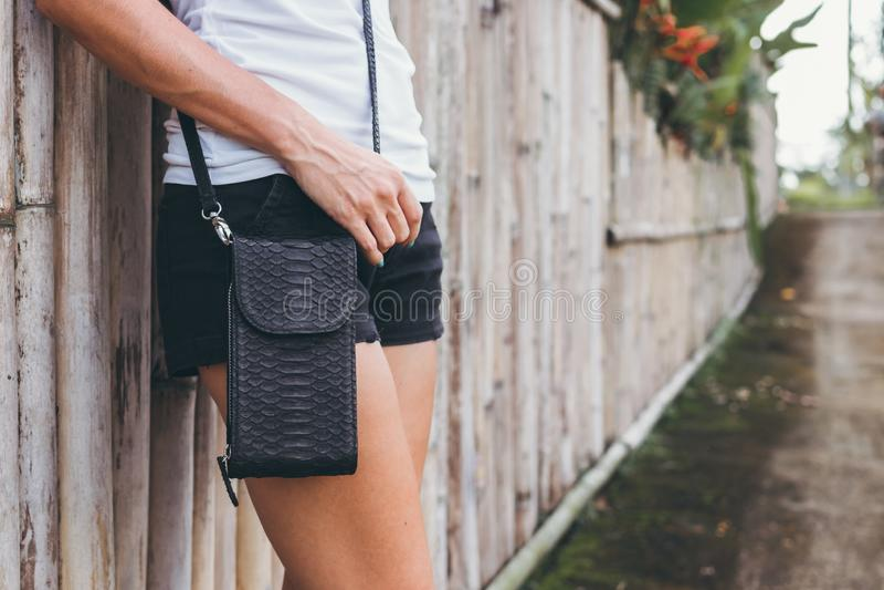 Young woman hands with stylish luxury snakeskin python handbag outdoors. Bali island. stock images