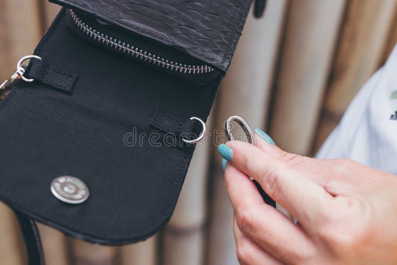 Young woman hands with stylish luxury snakeskin python handbag outdoors. Bali island. stock photos