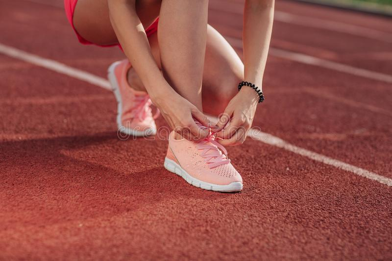 Young woman hands tie laces on her pink sport shoes on a stadium on a running path. White stripe near her. Close-up of tying shoes.  royalty free stock images