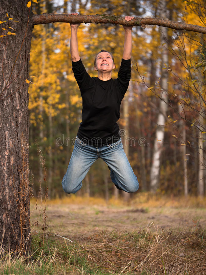 Young woman hanging on a branch with a strained expression on his face. On blurred background foliage royalty free stock photo