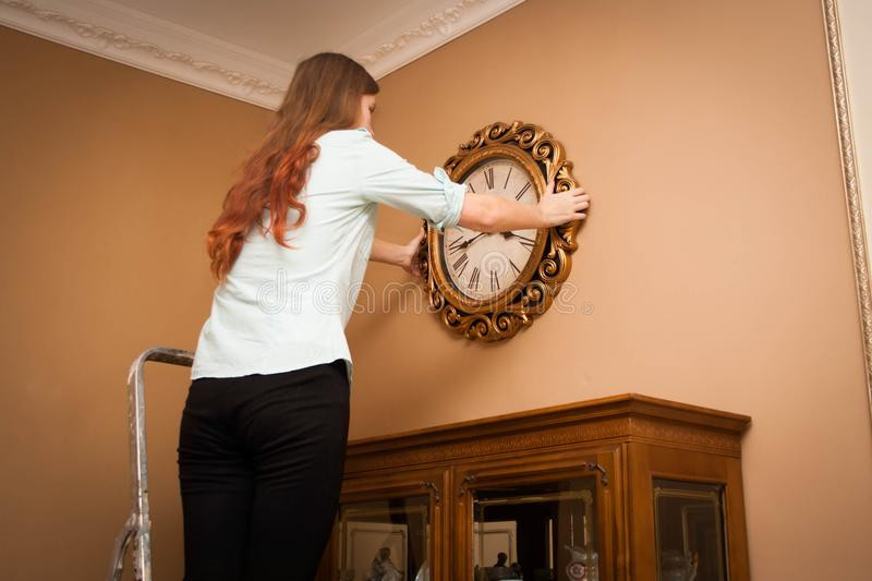 Young woman hanging a clock on the wall stock images