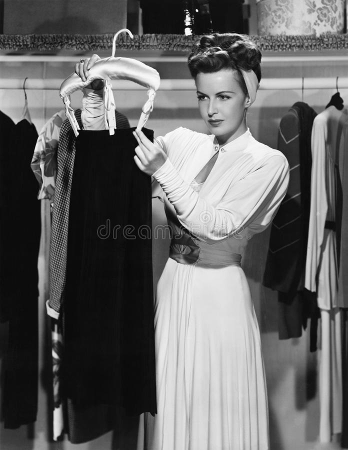 Young woman hanging up a skirt in the closet stock photography