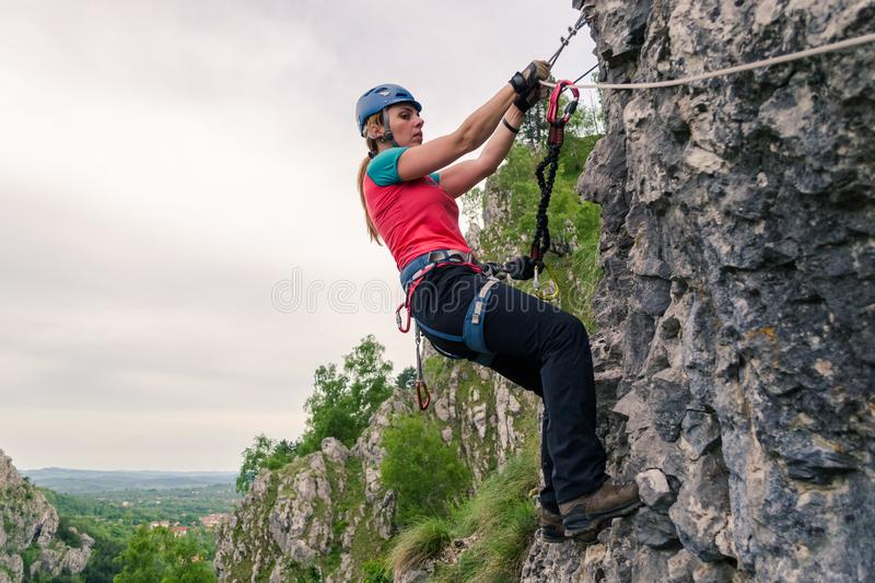 Young woman hanging from a via ferrata cable, while passing a difficult section, equipped with helmet, harness, kit. Klettersteig route at Baia de Fier royalty free stock images