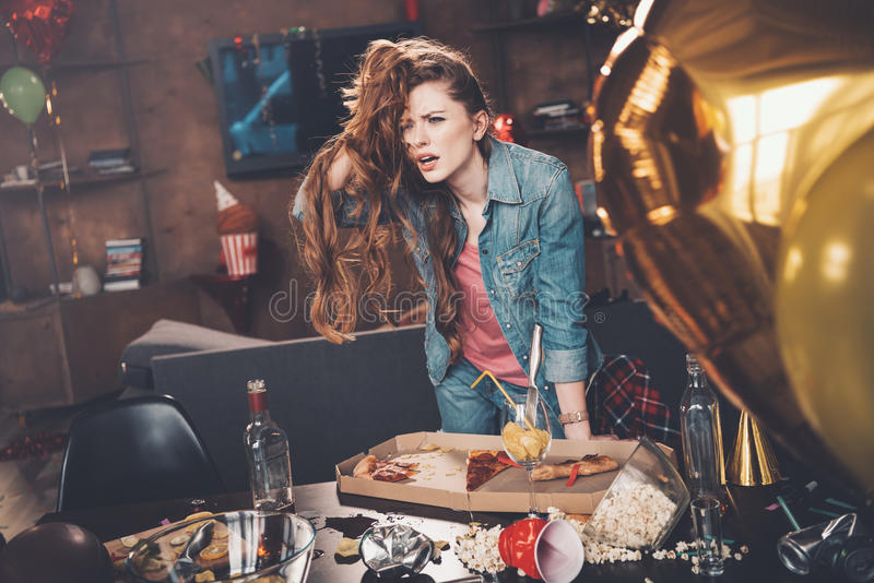Young woman with hangover leaning at messy table after party. Depressed young woman with hangover leaning at messy table after party stock photography