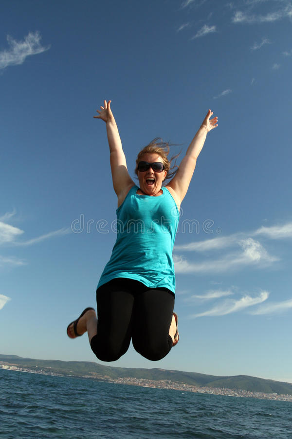 Download Young Woman In A Happy Jump Stock Photo - Image of glasses, happy: 26283046