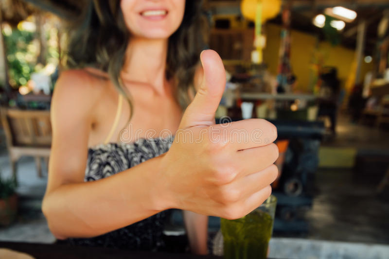 Young woman with happy smile showing thumb up. Girl showing a sign success stock photo