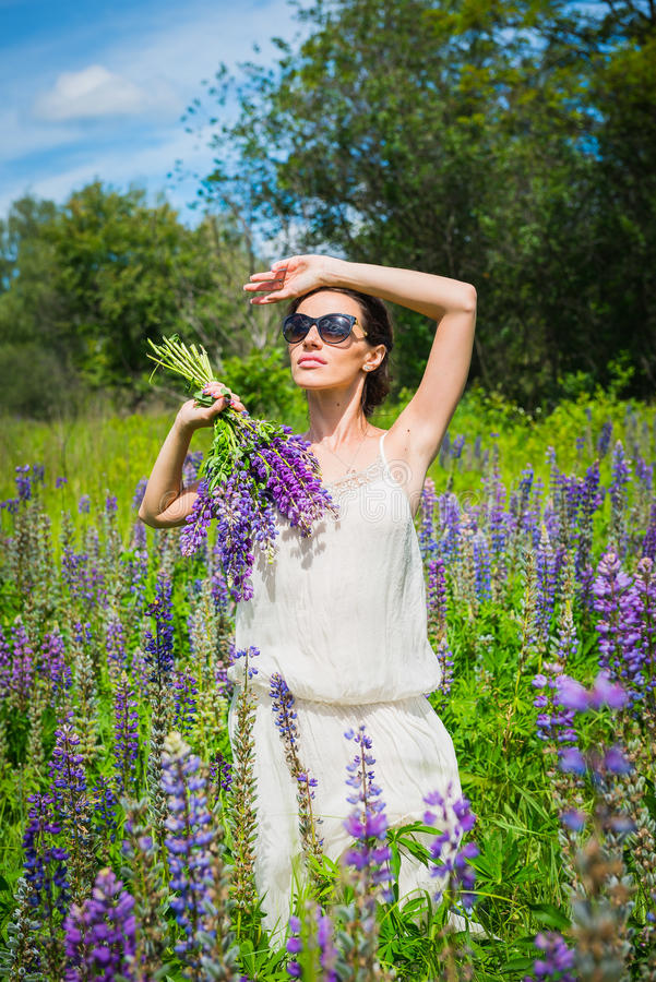 Young woman, happy, standing among the field of violet lupines, smiling, purple flowers. Blue sky on the background. Summer, with stock image