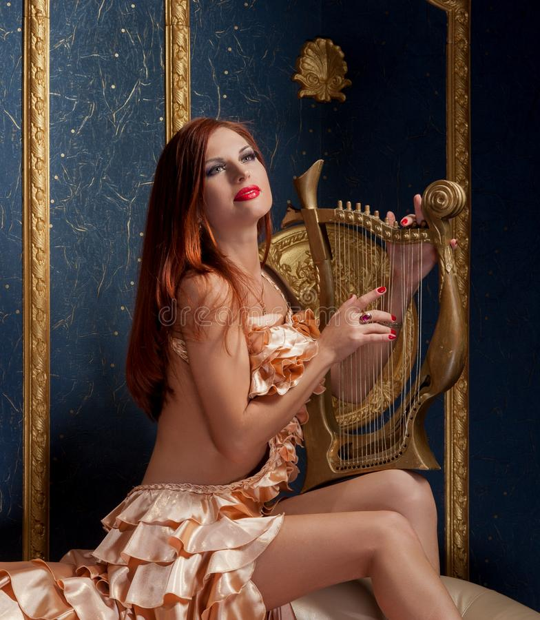 Young woman with harp. royalty free stock photo