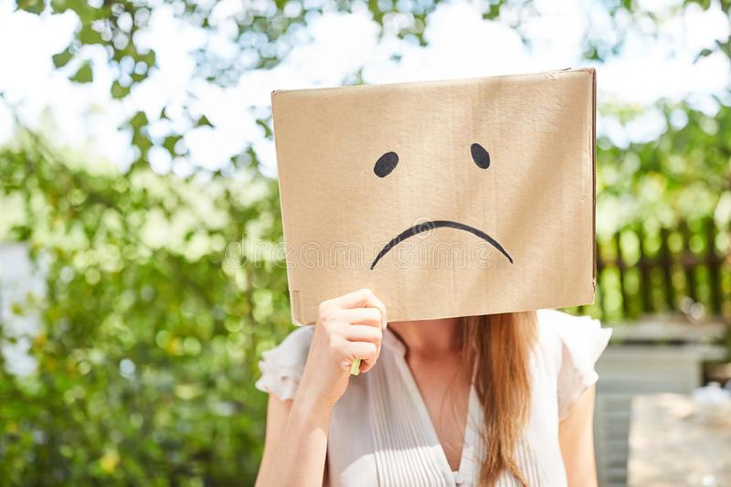 Young woman has face in cardboard box with sad face stock photos