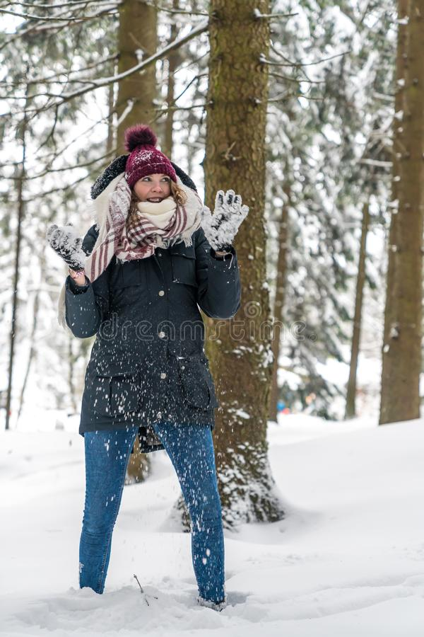A young woman has fun in a winterly forest. And holds a snowball in her hand royalty free stock image