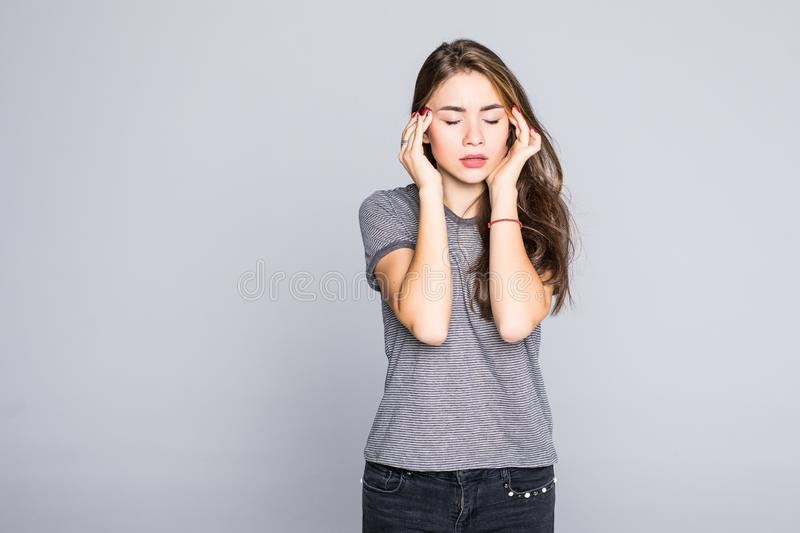 Young woman has headache on gray background. Young woman has headache, isolated on gray background stock photo