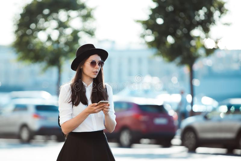 Young woman in a hat and with a backpack walks in the city and uses a smartphone. Hipster on a walk uses the phone and takes photos for social networks stock image
