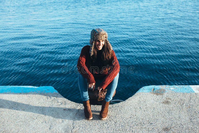 Young woman in hat and casual clothes sitting on pier stock photo
